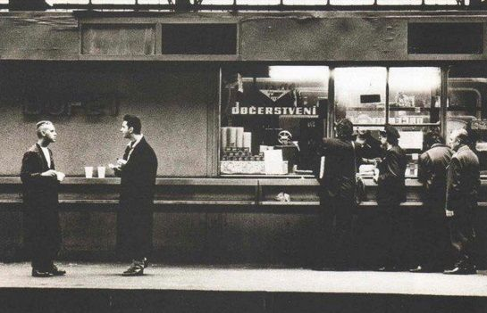 Depeche Mode in Prague - Martin L. Gore and Dave Gahan stand in front of fast food store in Prague's main station.   Martin L. Gore a Dave Gahan postávají v roce 1988 u stánku na pražském Hlavním nádraží - Fotografii pořídil dvorní fotograf kapely při nezapomenutelném koncertě depešáků v komunistické Praze -  Anton Corbijn