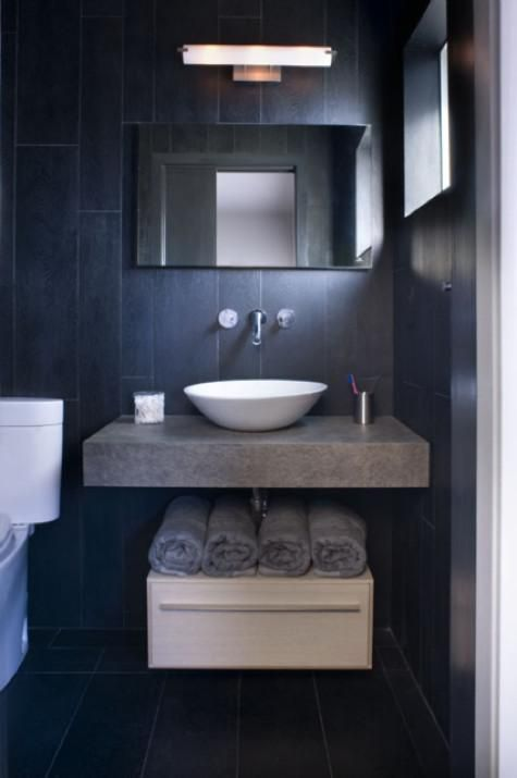 Simple white and gray fixtures complement the black slate tile in this bathroom by Dewitt Design Studios. Photo by Sharon Risedorph.