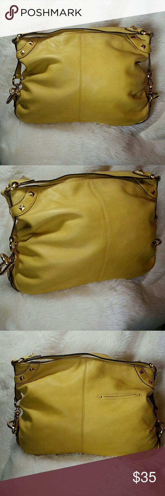 "B Makowsky Leather Yellow Hobo Handbag B Makowsky Leather Yellow Hobo Handbag. Buttery soft leather. Gold pyramid studs detailing. Although the bag is structurally sound with straps in great condition and a spotless interior, there are a few faded/dirt spots and marks on the handbag as well as a deep scratch within the leather on the front. Please see the first photo, the scratch is to the left of the center seam. 100% genuine leather. Large and slouchy. Zip top closure.  Measurements  16.5""…"