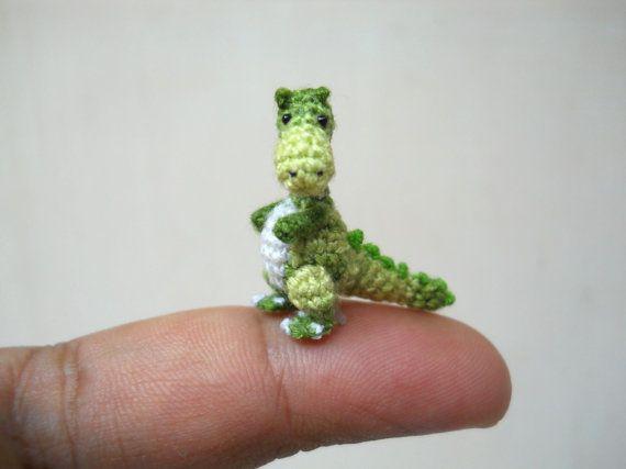 Bienvenue dans le petit monde du Jurassique.    Voici un bébé doux Tyrannosaurus en nuance de blanc et de vert.   Comme juste plus petit que les doigts, le petit dino est crocheté par mixte broderie fils avec des joints de bras peuvent être mobiles, ses yeux sont cousus plastiques fourrés noirs et farci de polyfil.    Taille : Aprox. 1 pouce (2,5 cm) de haut, 1,2 pouce (3 cm) de long.    Parfait pour nimporte quel DOLLHOUSE ou la MINIATURE de votre collection de minis minuscule animal et…