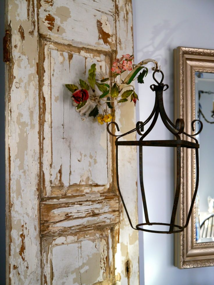 Hang a light,lantern or wall sconce from it.  Fabulous Old, distressed, door love!