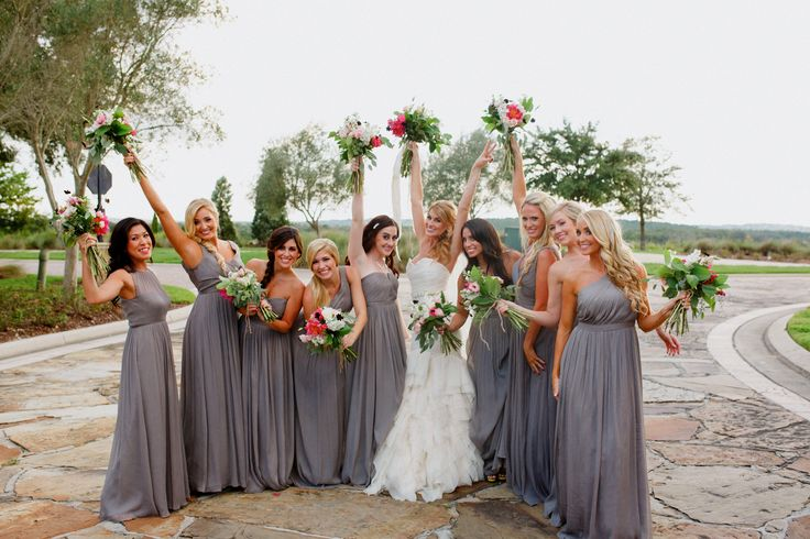 raising their pink ombre bouquets high, the bride and her bridesmaids celebrate the day.