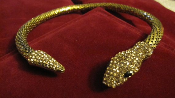 Light weight choker necklace made of hollow brass tube with the tail and head detailed with golden brown crystals