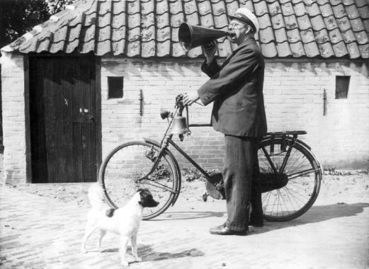 """Een dorps- of stadsomroeper verkondigde vroeger het nieuws in het dorp/de stad, toen er nog geen kranten bestonden. Hij bracht de bevolking op de hoogte van o.a. mededelingen van het stadsbestuur en van aanbiedingen van middenstanders.  Op deze foto een dorpsomroeper, West-Terschelling, 29 juli 1938. Op de foto maakt hij bekend dat het bergingsschip de """"Karimata"""" de eerste goudstaaf heeft gebaggerd van de vergane Lutine."""