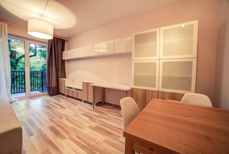 Aranżacja pokoju dziennego w minimalistycznym stylu. Praktyczny układ szafek z biurkiem.