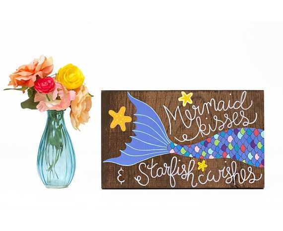 Mermaid sign, mermaid art, mermaid decor, mermaid painting, nautical nursery art, mermaid nursery art, mermaid bathroom  This hand painted rustic wood sign features a colorful mermaid tail and the quote Mermaid kisses & starfish wishes. The quote is written in a bright white paint. The end of the fin is a purple color. The mermaid tails scales are outlined with black ink and three orange and yellow starfish surround it. This would look super cute in a childs nursery and would make a great…