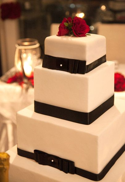 Black and white marzipan covered wedding cake with edible pearls and real red roses