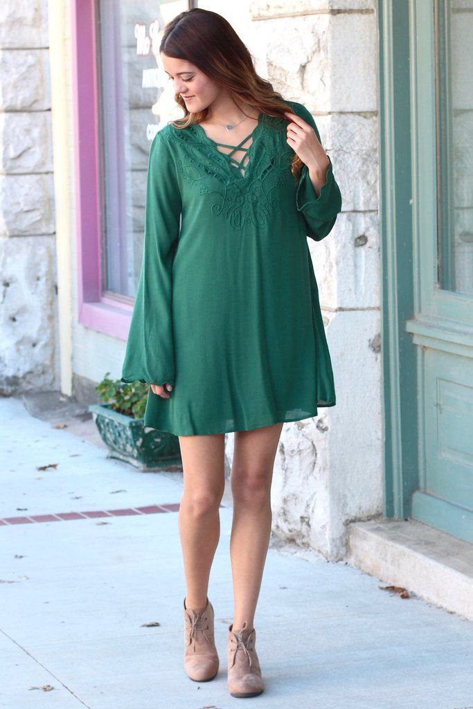 Long, bell sleeve dress with a strappy v-neckline and embroidery. Loose fit. Lined. Green in color. We love this dress for fall with boots or booties.
