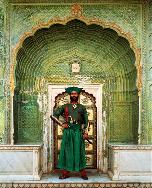 A guard wearing a Rajputi uniform bravely guards the Peacock Door at City…