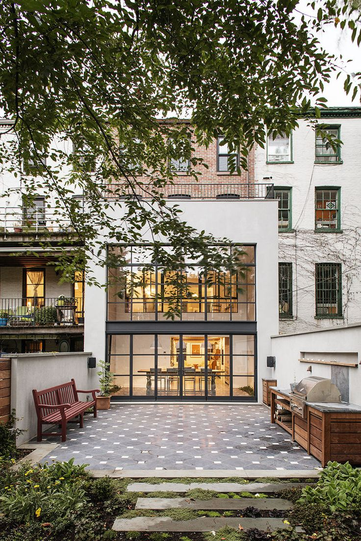 Outdoor patio with Lapicida tumbled black limestone and white Carrara marble inserts outside Brooklyn renovation by Elizabeth Roberts.
