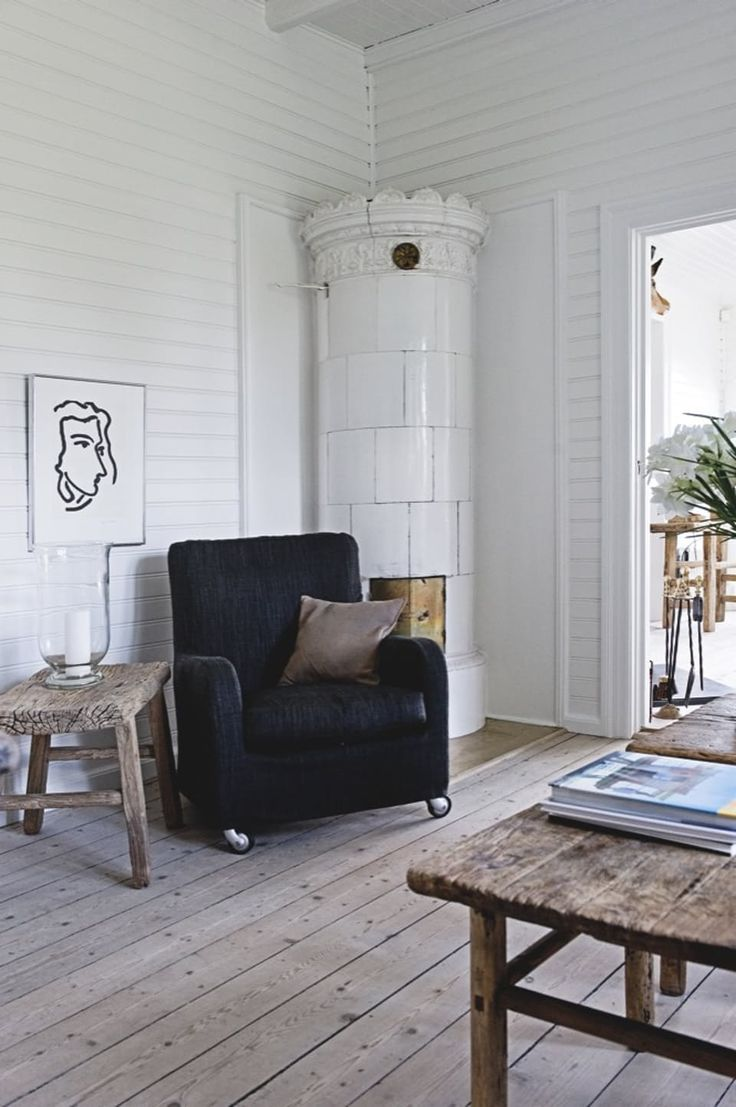 Cozy corner in a nordic look - comfortable armchair in front of a white tiled stove with raw wooden tables.