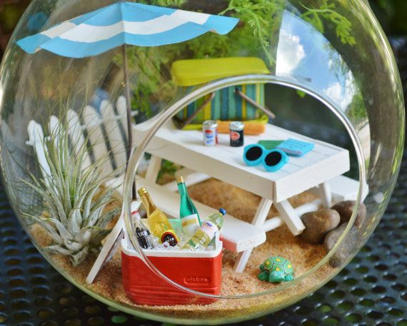 ♥´¨) ¸.•´ ¸.•*´¨)¸.•*¨) (¸.•´ (¸.•`♥~ Want to go on a picnic? With this terrarium.... Everyday is a Picnic!!! :)  This is the cutest little picnic table and picnic basket! Includes 2 drinks, baguette, 2 books, sunglasses, and cute little kitten! May choose dog or turtle. see last photo. Leave message at checkout. Such a magical place with the picket fence, table, tree floral spray and 2 little air plants. You may also choose this terrarium with a Cooler with ice and 2 more drinks in it. ...