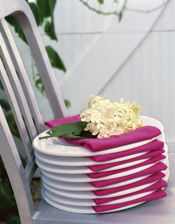 stack of plates with bright pink napkins on each one and topped with a bunch of small white flowers
