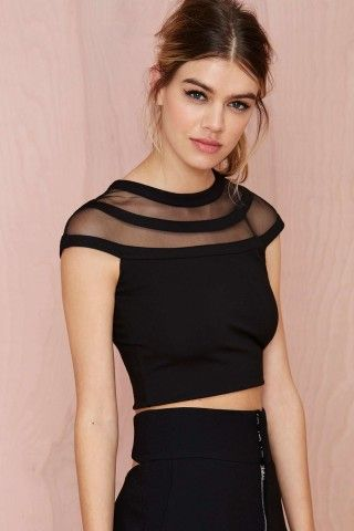 This black crop top is perfect for showing off those toned arms. It has mesh detailing at top with opaque black panels, stretch fabric, and cap sleeves. Wear it with leather pants, suede pumps, and an oversized leather clutch.*Viscose/Nylon/Spandex *Runs true to size *Model is wearing smallest size available *Hand wash cold *Imported