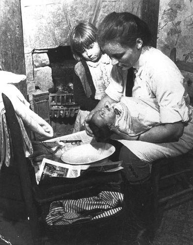 Nurse-midwife gives a newborn its first bath. Note that the nurse wears a white butcher's apron over her riding uniform. (University of Kentucky Photographic Archives)