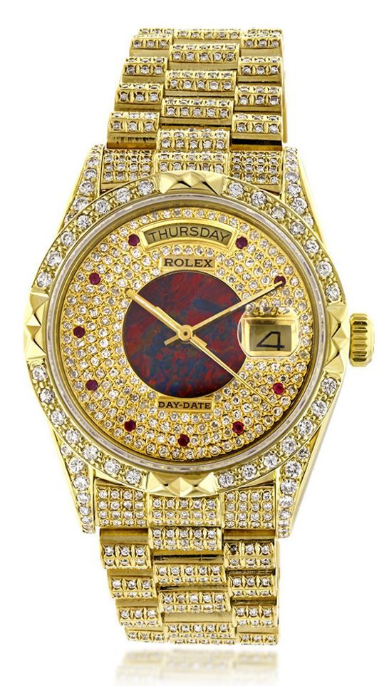 This lavish Mens Rolex Oyster Perpetual Day-Date Custom Diamond Watch is made of solid 18K yellow gold and showcases 14 carats of custom after market set diamonds. Featuring a fully iced out look, this unique Rolex watch has an exquisite custom dial encrusted with diamonds, rubies and opal. This Rolex watch is secured with an 18K rose gold hidden fold clasp and is conveniently water resistant to 30 m (100ft).
