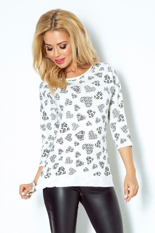 Oryginalny model bluzki damskiej, wykonanej z przyjemnego w dotyku materiału z wzorem w serduszka z napisami I LOVE YOU oraz finezyjnym wiązaniem na boku. W połączeniu ze spodniami bluzka tworzy elegancką kreację sportową. #bluzka #damska #sportowa #kobieta #moda #trendy #wzory #biel