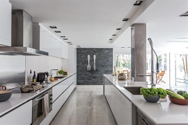 """Una cocina con detalles de vanguardia  En esta cocina se luce (y al mismo tiempo se """"esfuma"""" discretamente contra el fondo) el amoblamiento de PVC brillante de la línea 'Gourmet' de De Otro Tiempo, con zócalos de acero"""