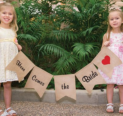 The Here Comes the Bride Burlap Banner can be carried down the aisle by the little flower girl and ring bearer.