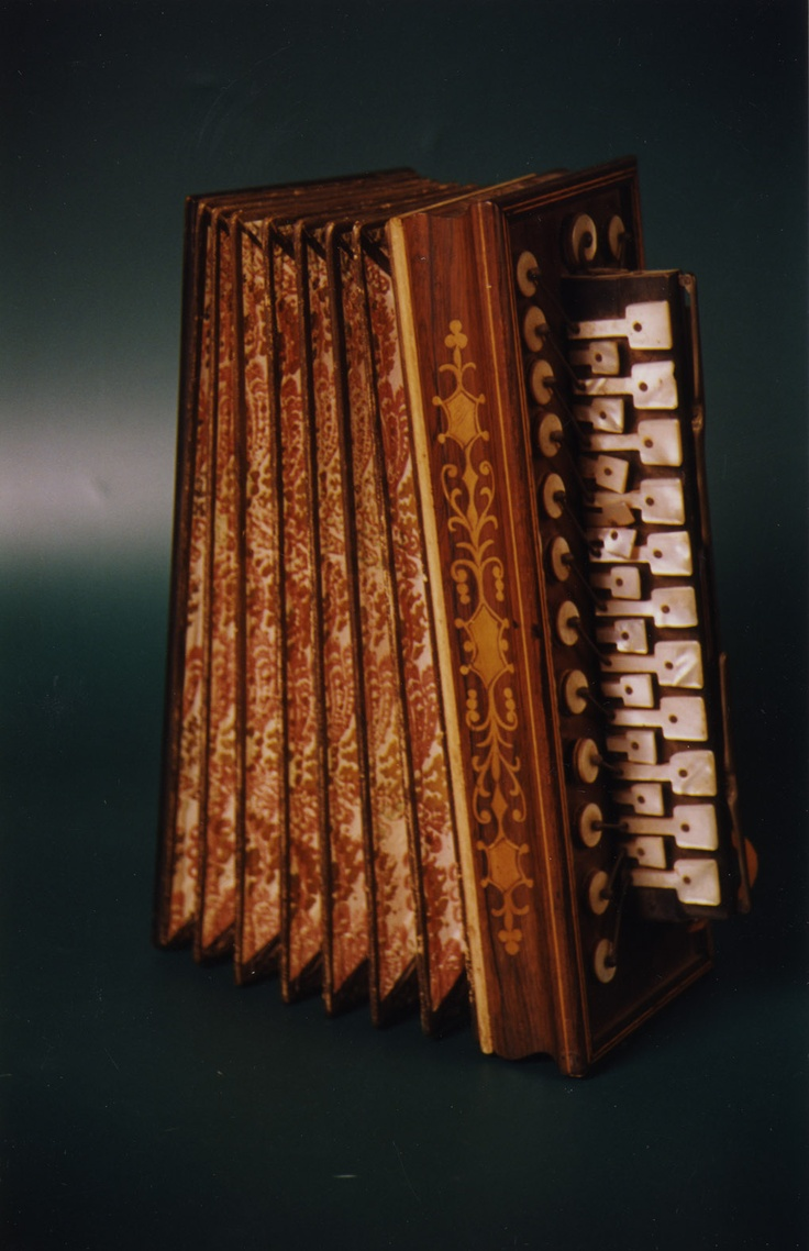 Name ACCORDION  Classification Aerophones  'Other name' Accordion  'Culture group' French?  'Culture group place' France  Description:  Wooden handles with textile bellows, mother of pearl touches and brass keys.  'Associated date' Manufacture 1850