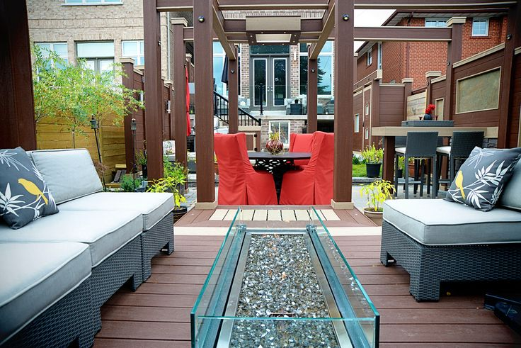A sleek gas-powered fire feature with glass accents makes a welcoming focal point for this lounge area. Deck Design by Paul Lafrance Design.