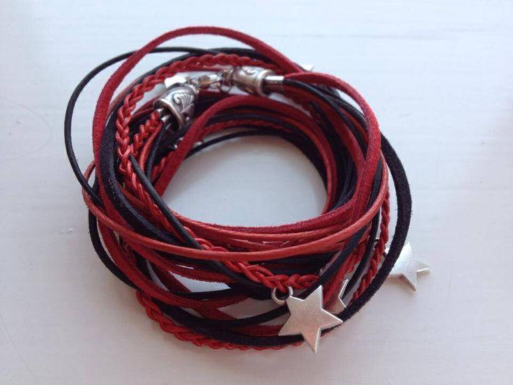 Veter wrap armband in rood en zwart met metalen sterren in er gevlochten. Afgewerkt met metalen sierkappen en een lobster sluiting. €15,00.