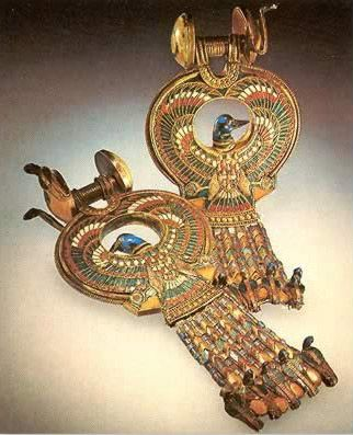 Earrings from the tomb of Tutankhamun. Gold and enamel, inlaid with blue glass and semiprecious stones. They have wear marks consistent with having been worn by the king during his lifetime on a regular basis. Earrings were a relatively new fashion for royalty at the time of Tutankhamun and it is thought that they were worn by women and boys who discarded them when becoming a man. Tutankhamun was only 18 at the time of his death and so barely past the time to discard them. 1332-1323 BCE
