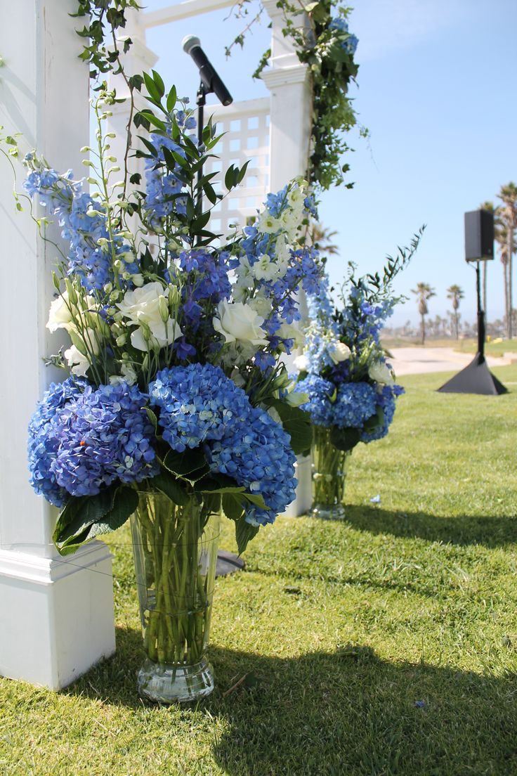 A bridal arch. On the beach. These arrangements were used in the reception area after the ceremony.  This is from a ocean themed wedding. Fresh white and blue.  White Orchids, blue and white Hydrangea, white lisianthus , white roses,  blue delphinium , Ivy,  Lemon leaf.