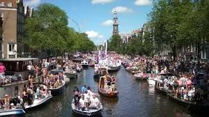 Amsterdam, Netherlands.....A Gay Pioneer destination Amsterdam has lone of the largest European Gay Pride parades and perhaps the only parade on water. Here we see the floats coming down the canal.  Inclusion has always been a part of the culture in Amsterdam. There are gay bars, hotels, and clubs. There's even a monument called the Homomonument, dedicated to gays and lesbians who lost their lives in World War II. Next to the monument is the Pink Point, the city's offi