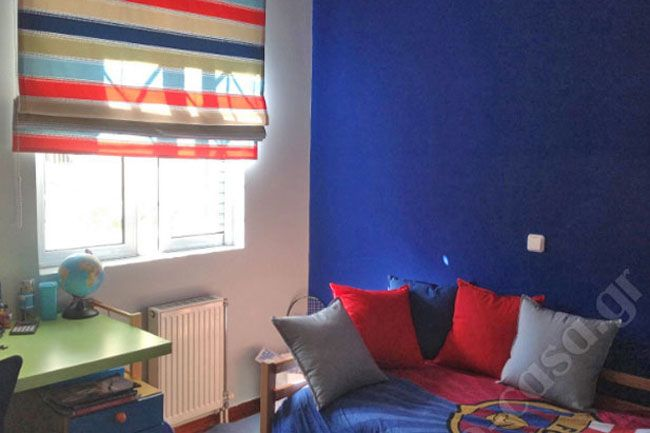 Αν και τα δωμάτια για τους νεαρούς είναι συνήθως πιο λιτά από τα κοριτσίστικα αυτό δεν σημαίνει ότι είναι περιορισμένες οι επιλογές μας.  Μία λύση είναι να ξεκινήσουμε από ένα βασικό, έντονο χρώμα που θα κυριαρχήσει στον χώρο. Στο δωμάτιο του Κωνσταντίνου είναι το μπλε. Συμπληρώνουμε με ένα δεύτερο χρώμα - εδώ έχουμε γκρι ανοιχτό και βάζουμε και ένα τρίτο σαν πινελιά για να φωτίσει - τι πιο φωτεινό από το κόκκινο.