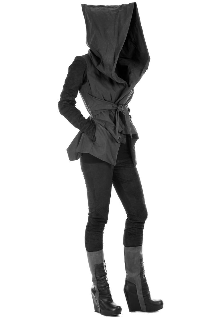 Female wearing a short coat with a large hood. The whole clothing is simple, with the usage of grey scale and none complex designs to the clothing.
