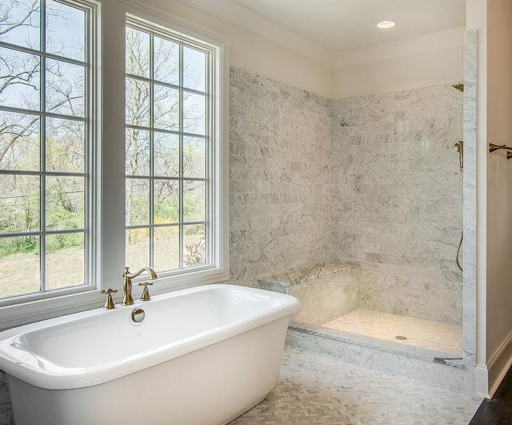 Master bathroom features a freestanding tub placed atop a marble herringbone tiled floor next to an open walk-in shower clad in gray marble subway tiles fitted with a L shaped marble shower bench.