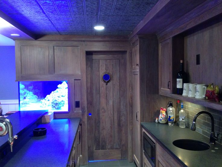 Porthole and custom 300 gallon aquarium.  Distressed walnut cabinets and hone black granite countertops.