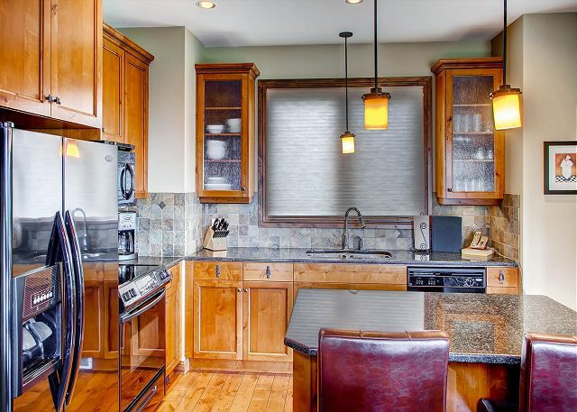 Big White Vacation Rentals | Awesome kitchen in this delightful ski in / ski out residence in Big White. There is parking for 3 vehicles. One in the carport and 2 in the driveway.