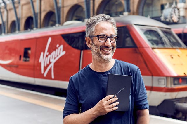 David Baddiel outside with his pen and pad, on a mission to get inspiration