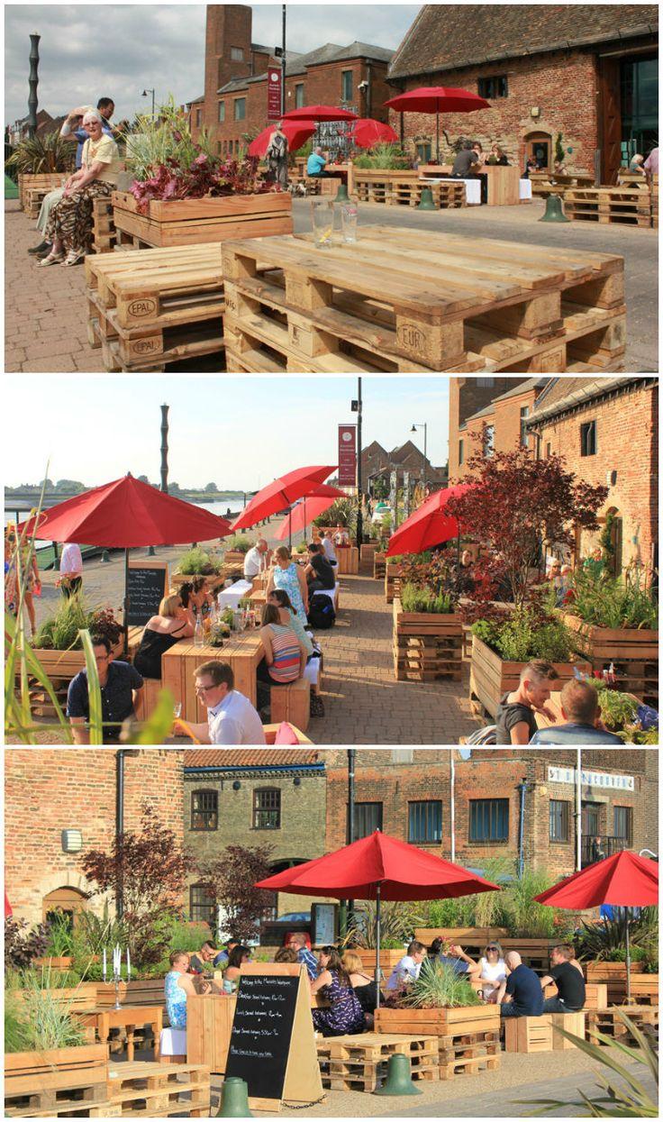 """Conception et réalisation d'une terrasse sur un ancien quai de marchandise de King's Lynn (UK) par le collectif les Jardiniers Nomades. Les tables, fauteuils, bancs et bacs de plantations sont une déclinaison de la palette Europe. [symple_box color=""""gray"""" fade_in=""""false"""" float=""""center""""…"""