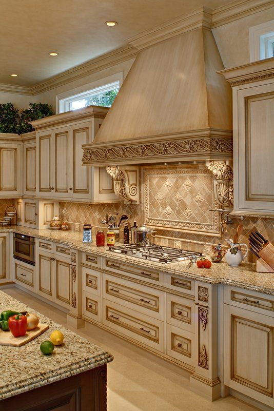 X X High- L shaped kitchen cabinetry with glaze and antiquing. Mahogany  Island has carved elements with paneling, drawers