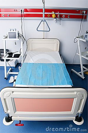 Empty hospital bed surrounded by medical accessories.