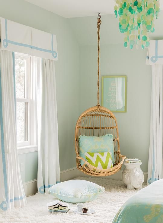 Blue and green teen's bedroom features pale green walls framing windows dressed in white pleated valances with blue Greek key trim paired with matching curtains flanking a Two's Company Hanging Rattan Chair adorned with a blue and green pillow and a green chevron pillow next to a white elephant table, Serena & Lily Ellie Side Table, place under a blue and green Keep Calm and Carry On Print illuminated by a PB Teen Capiz Chandelier Blue/Green.