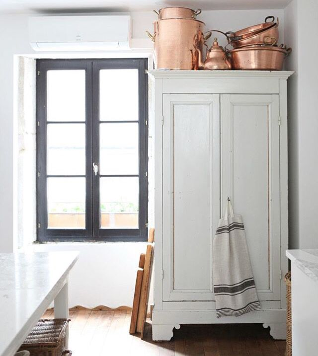 copper pots and pans and antique pantry cupboards
