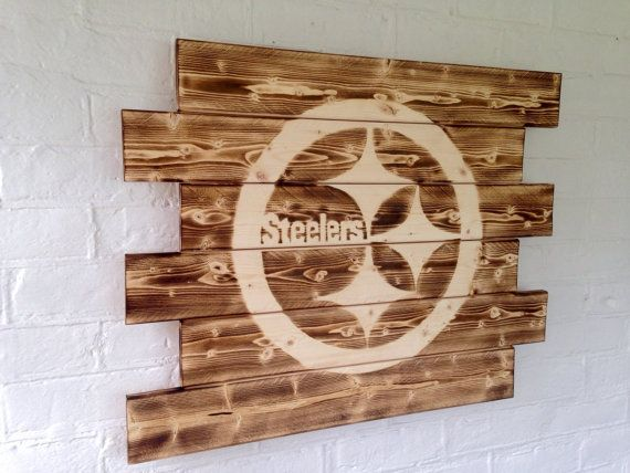 Rustic burned wood Pittsburgh Steelers Football sign. Each sign is hand torched to achieve a rustic barn wood look and feel. Each sign is hand made and wood grains may differ from picture to picture as each piece is unique. *Sign is approx. 27 x 21 and comes with strung with picture hanging wire for easy hanging.