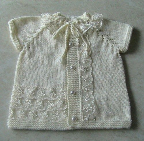 Plain white baby vest with embellishments: openwork on raglan lines, broderie, pearl buttons