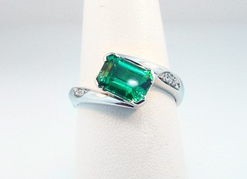 """A customized """"Cosmic"""" ring with an emerald center- by Mark Schneider."""