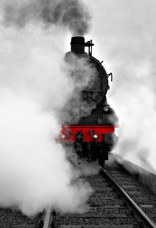 """A brilliant pop of red peeks through the steam of an old-fashioned locomotive. 