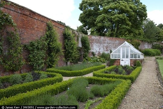 Greenhouse with high brick wall and formal garden.
