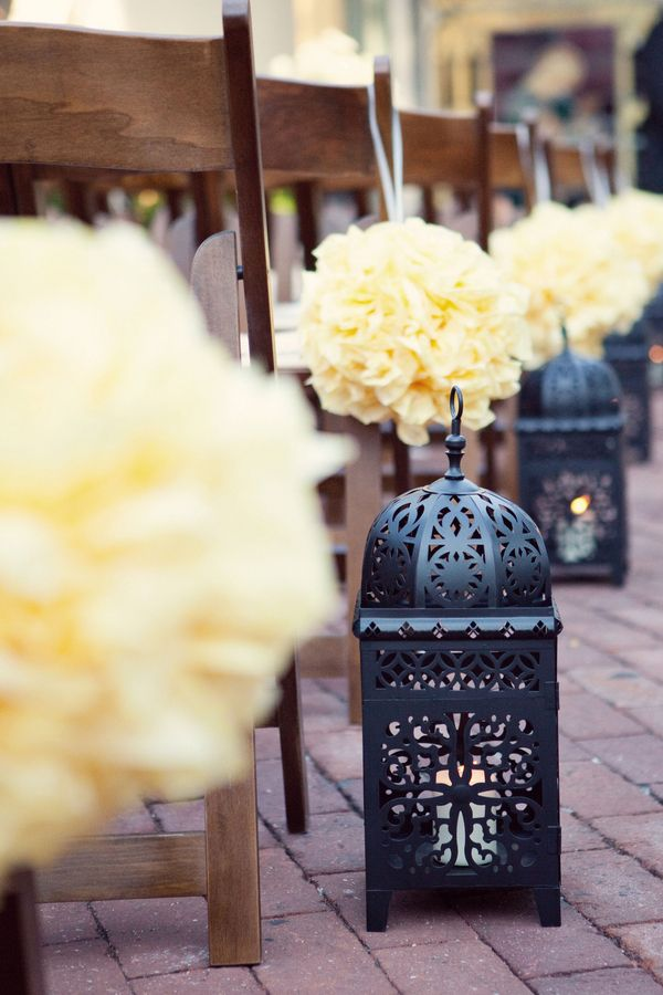We love the mixture of delicate yellow poms contrasted with the iron Moroccan lanterns.
