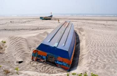 An overturned boat, non-functional and abandoned in the beaches of Konkan.