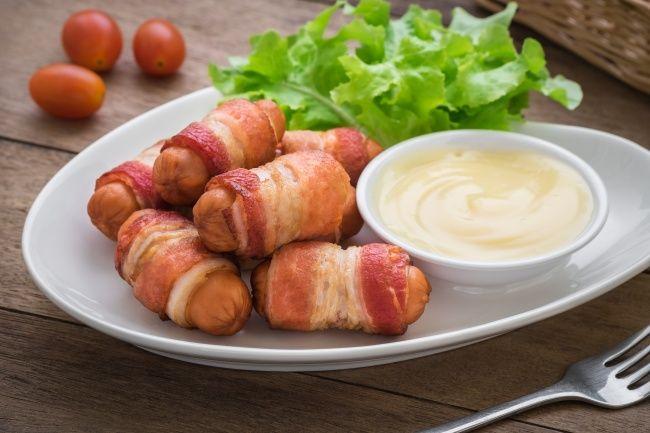 Разрезать каждую сосиску на три части, обернуть каждую беконом или тонко нарезанной ветчиной. Закрепить зубочистками. Выпекать 10–15 минут в духовке. Подавать с любым сливочным соусом.