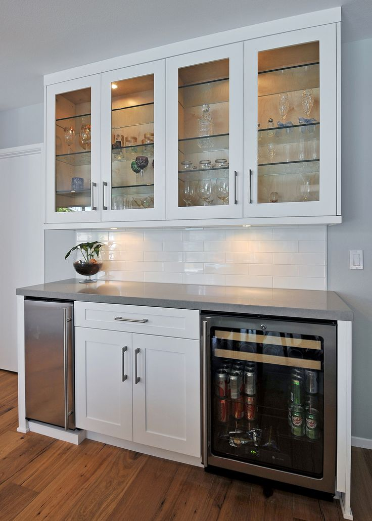 White modern serving and bar area in the dinning space that compliments the open kitchen. White shaker door lower cabinets with glass inserts on uppers. Under cabinet wine /beer fridge with separate under cabinet freezer.