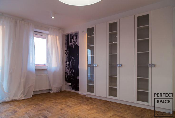 Aranżacja salonu będąca przykładem połączania starego z nowym: deski podłogowe układane w poprzek, tapeta z wizerunkiem Charliego Chaplina oraz przeszklona biblioteczka
